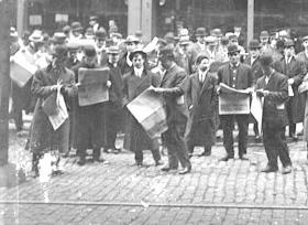 Men and boys standing and reading newspapers outside the Chicago Daily News building at 123 North Wells Street, 1911